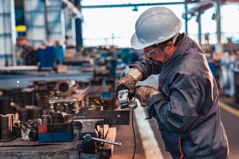 Skilled manufacturing worker grinding metal part.